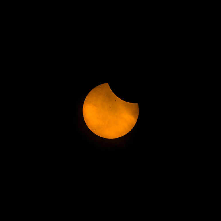 I caught an early part of the eclipse (20 minutes after C1) through the clouds along with some sunspots. (32.52 KB)